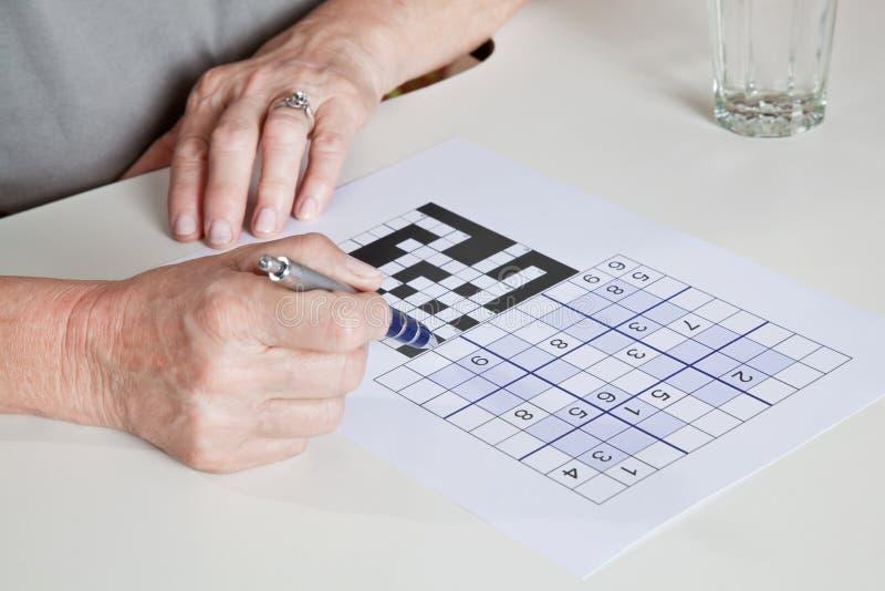 Donna matura che gioca puzzle di Sudoku immagine stock