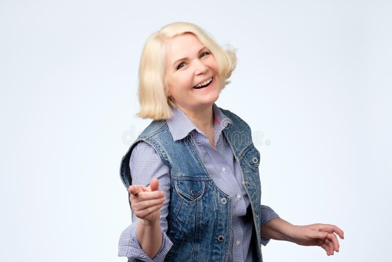Donna matura che indica dito e sorriso a trentadue denti Colpo dello studio immagini stock