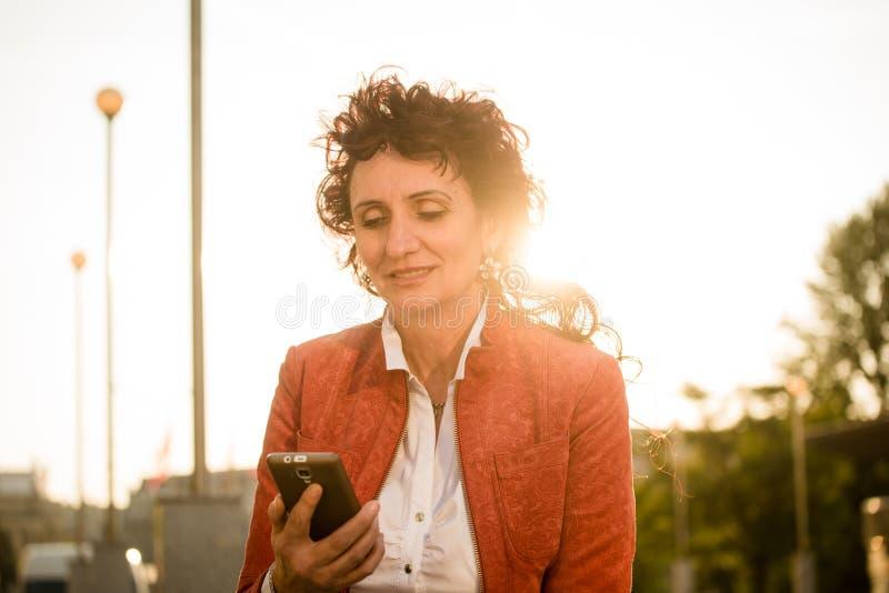 Donna matura che osserva al telefono il tramonto immagini stock libere da diritti