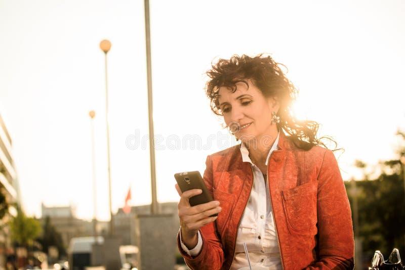 Donna matura che osserva al telefono il tramonto fotografie stock