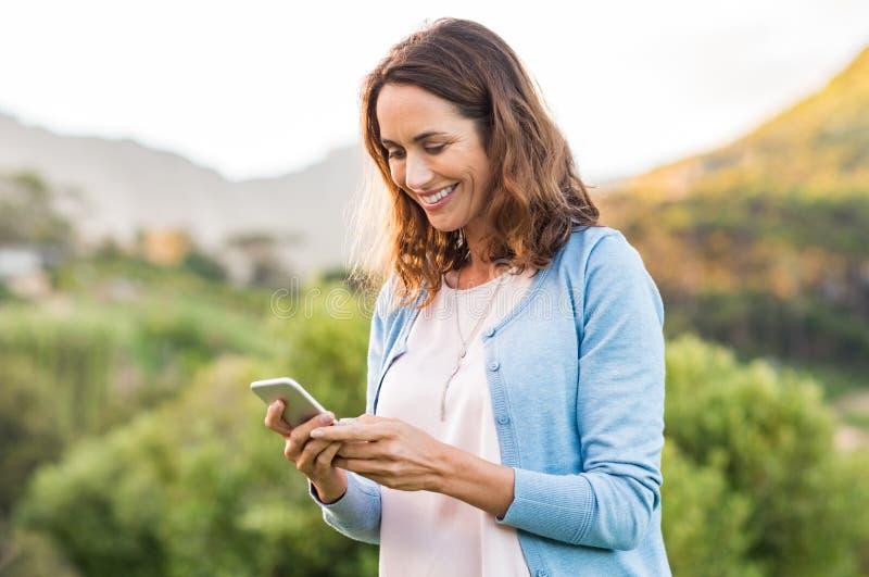 Donna matura che per mezzo del cellulare fotografie stock libere da diritti