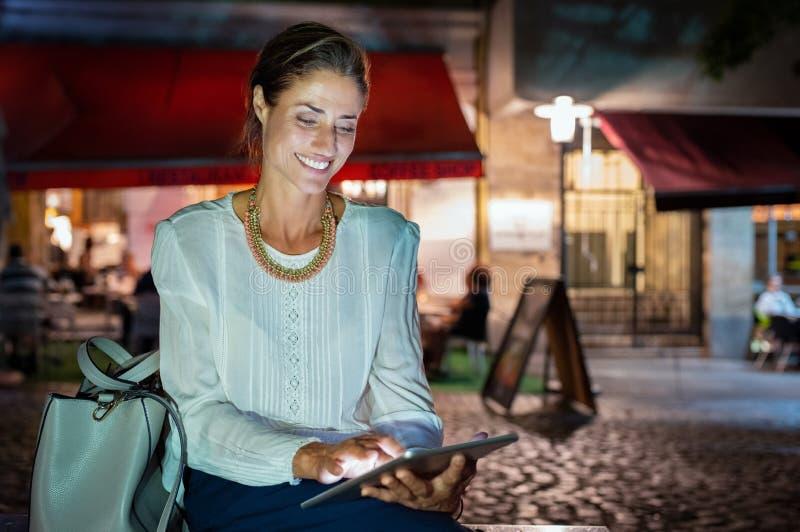 Donna matura che per mezzo della compressa digitale alla notte immagini stock libere da diritti