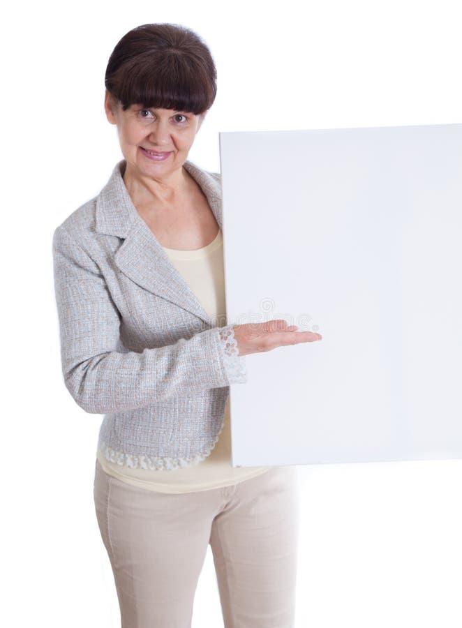 Donna matura che si appoggia insegna bianca Ritratto contro di fondo bianco immagine stock