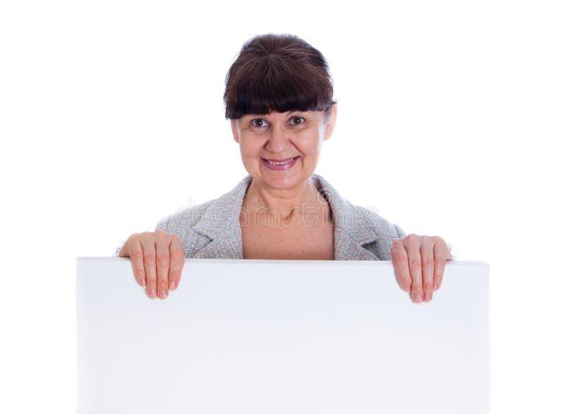 Donna matura che si appoggia insegna bianca Ritratto contro di fondo bianco immagini stock