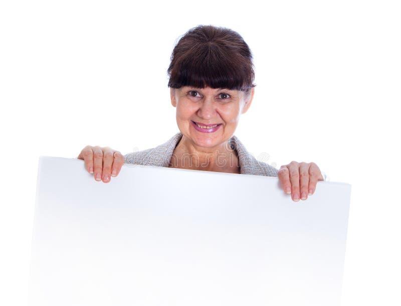 Donna matura che si appoggia insegna bianca Ritratto contro di fondo bianco fotografia stock