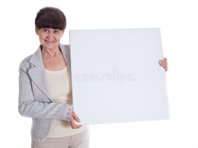Donna matura che si appoggia insegna bianca Ritratto contro di fondo bianco immagine stock libera da diritti