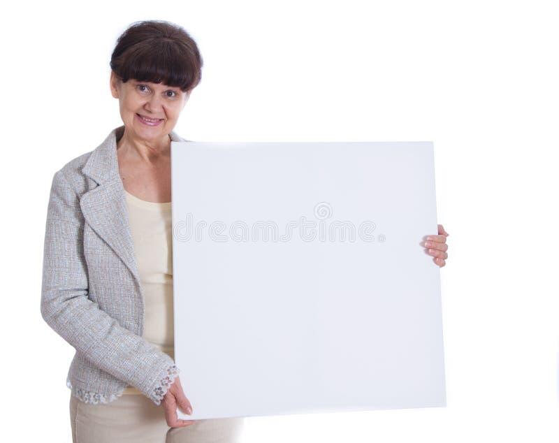 Donna matura che si appoggia insegna bianca Ritratto contro di fondo bianco fotografia stock libera da diritti