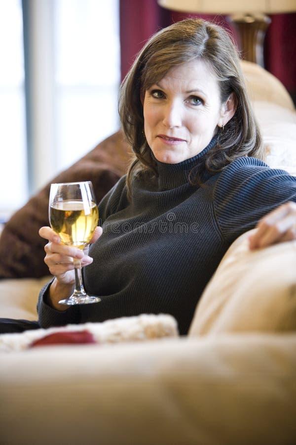 Donna matura che si distende sul vino bevente del sofà immagine stock libera da diritti