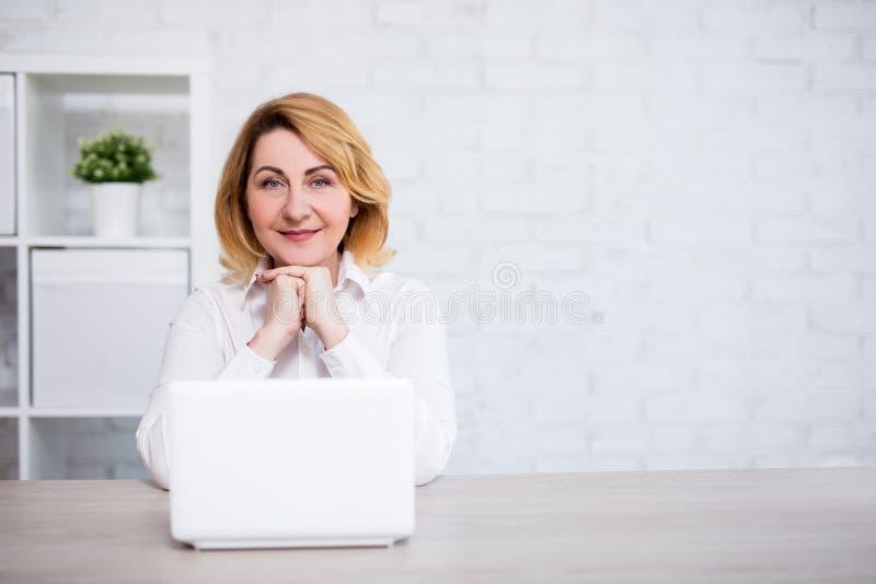 Donna matura che si siede con il computer portatile in ufficio o in salone moderno - spazio della copia sopra la parete bianca fotografie stock