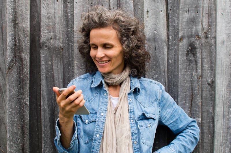 Donna matura che sorride con il telefono fotografia stock