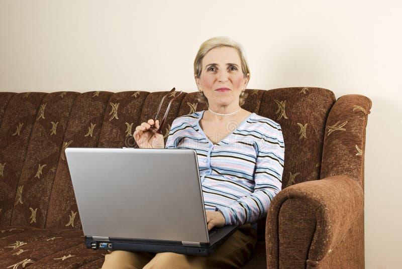 Donna matura che usando la casa del computer portatile fotografia stock libera da diritti
