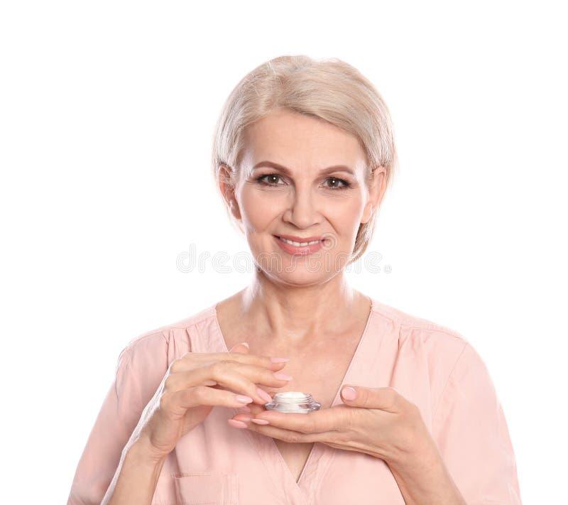 Donna matura con il barattolo della crema di fronte antinvecchiamento fotografie stock