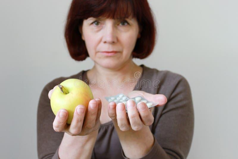 Donna matura con le pillole e Apple immagine stock