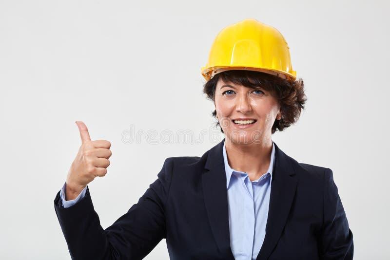 Donna matura dell'ingegnere che mostra i pollici su immagini stock