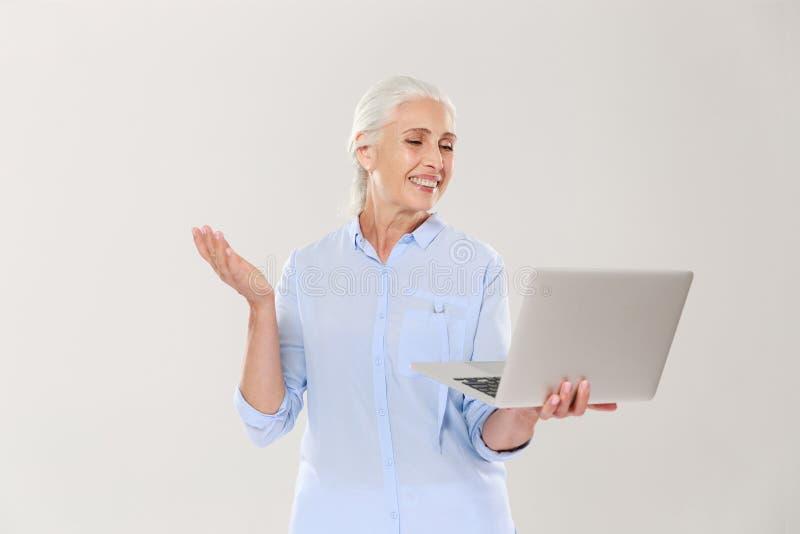 Donna matura divertente che per mezzo del computer portatile isolato sopra bianco immagini stock libere da diritti