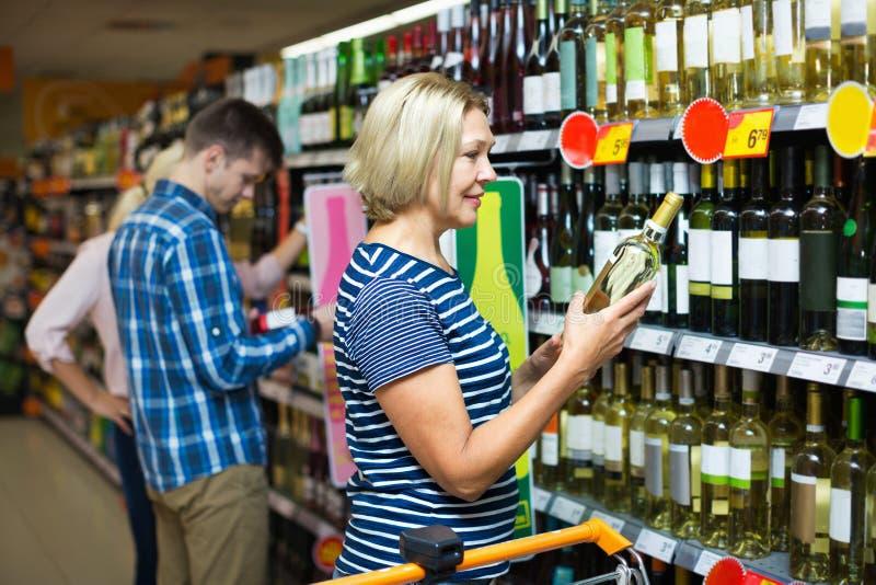 Donna matura felice alla sezione del vino fotografie stock libere da diritti