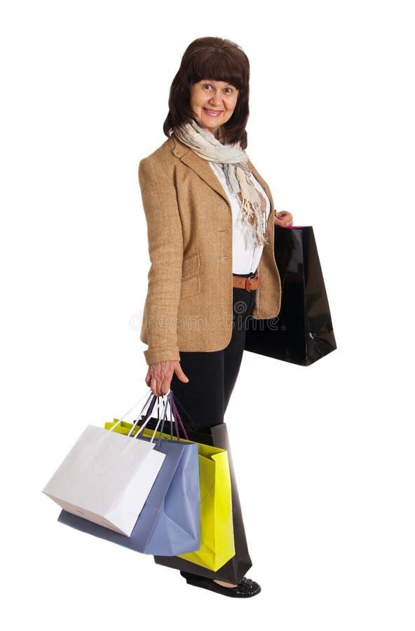 Donna matura felice che cammina con gli acquisti di acquisto immagini stock