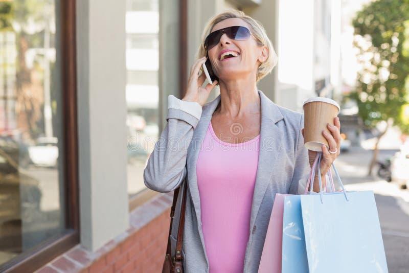 Donna matura felice che cammina con i suoi acquisti di acquisto immagini stock