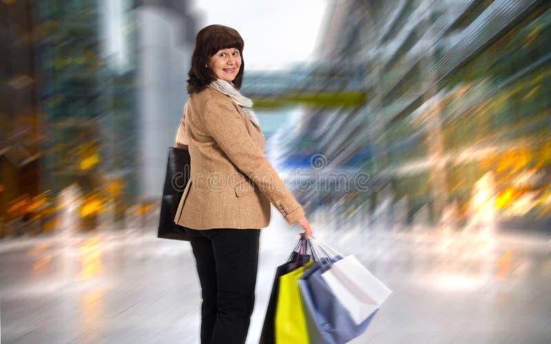 Donna matura felice che cammina con i suoi acquisti di acquisto fotografia stock libera da diritti
