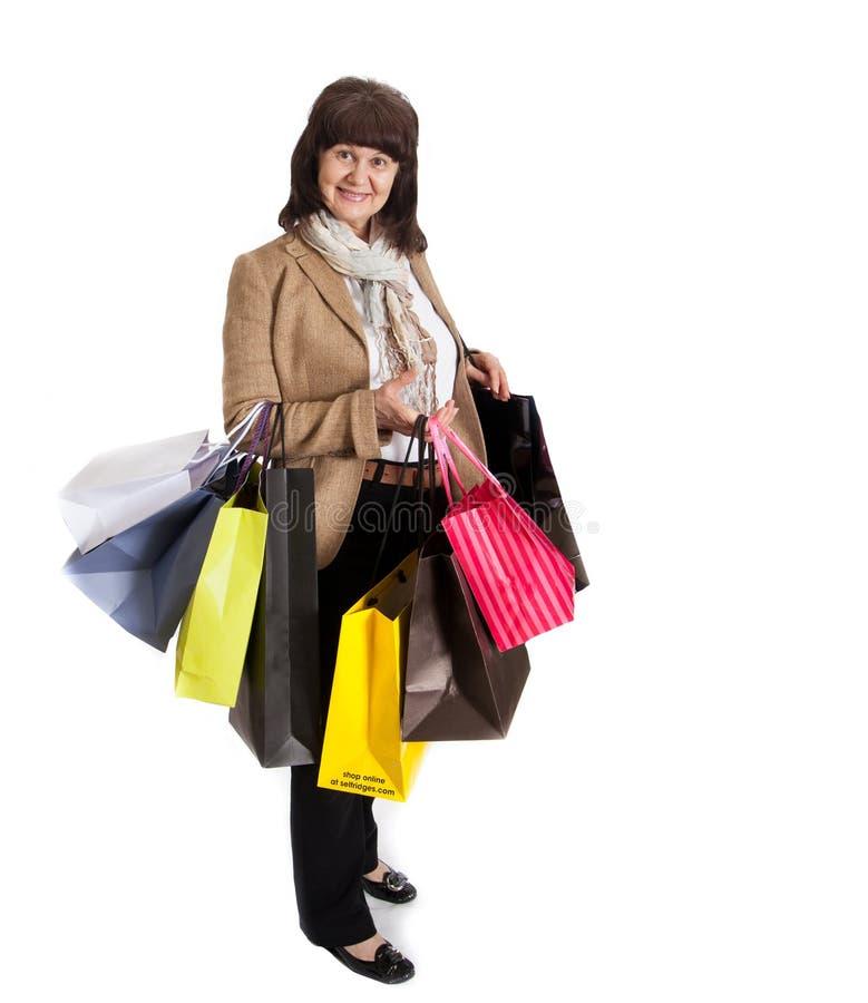 Donna matura felice che cammina con i suoi acquisti di acquisto fotografie stock libere da diritti