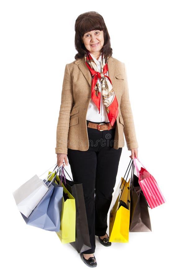 Donna matura felice che cammina con i suoi acquisti di acquisto immagine stock