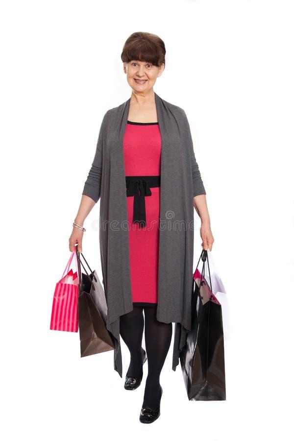 Donna matura felice che cammina con i suoi acquisti di acquisto fotografia stock