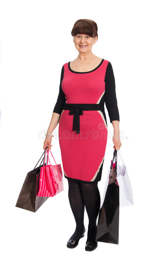 Donna matura felice che cammina con i suoi acquisti di acquisto immagini stock libere da diritti