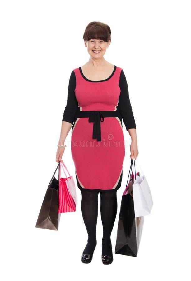 Donna matura felice che cammina con i suoi acquisti di acquisto immagine stock libera da diritti