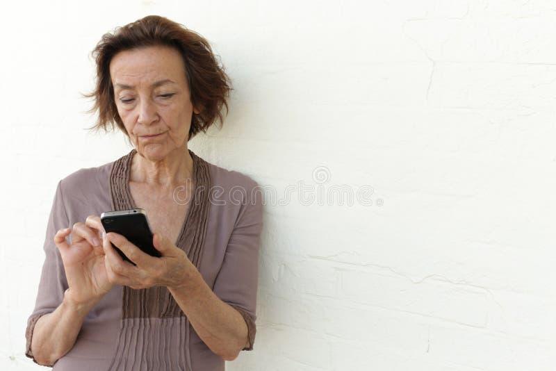 Donna matura infastidita con il suo telefono immagine stock