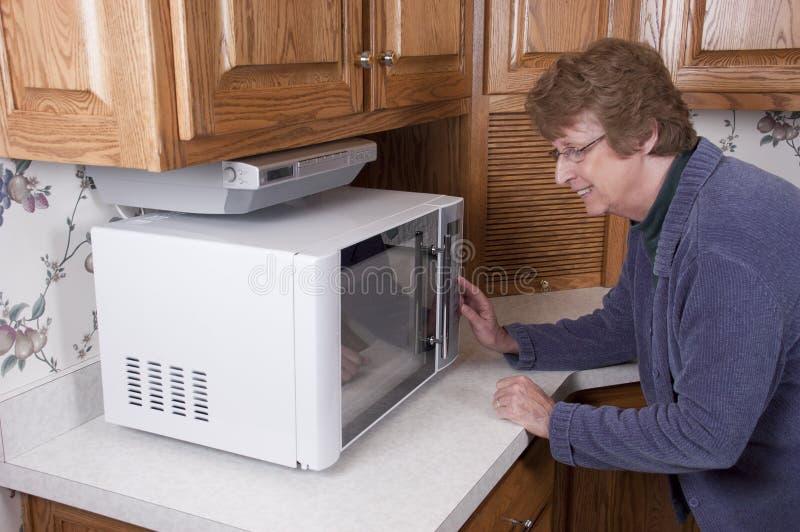 Donna matura maggiore che cucina la cucina del forno a microonde fotografia stock libera da diritti