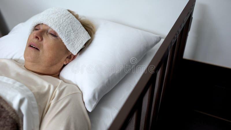Donna matura malata che si trova nel letto di ospedale con la compressa sulla fronte, sulla febbre o sull'influenza fotografia stock
