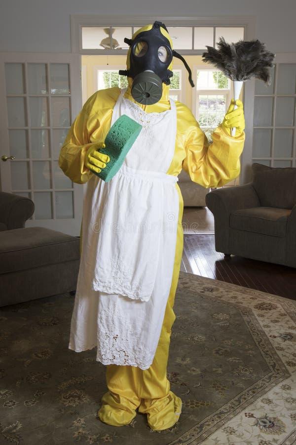 Donna matura nel vestito della stuoia di Haz con lo spolveratore e la spugna della piuma immagini stock