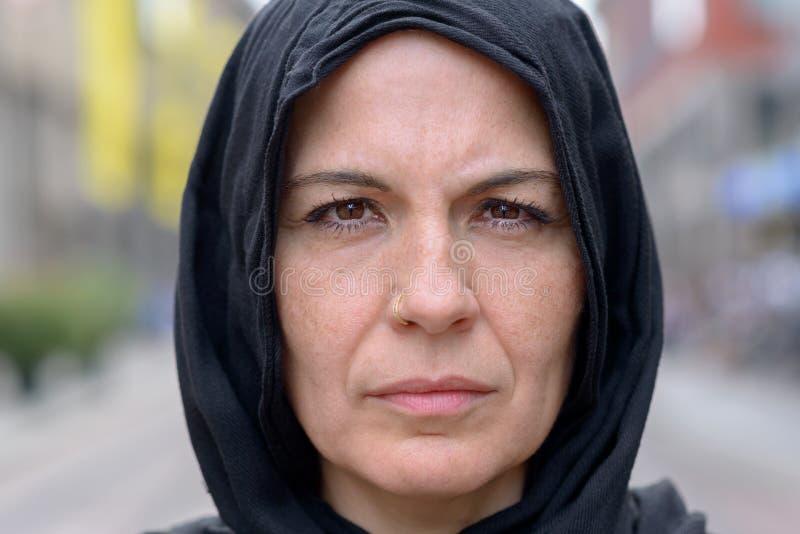 Donna matura pensierosa che porta una sciarpa capa nera fotografia stock