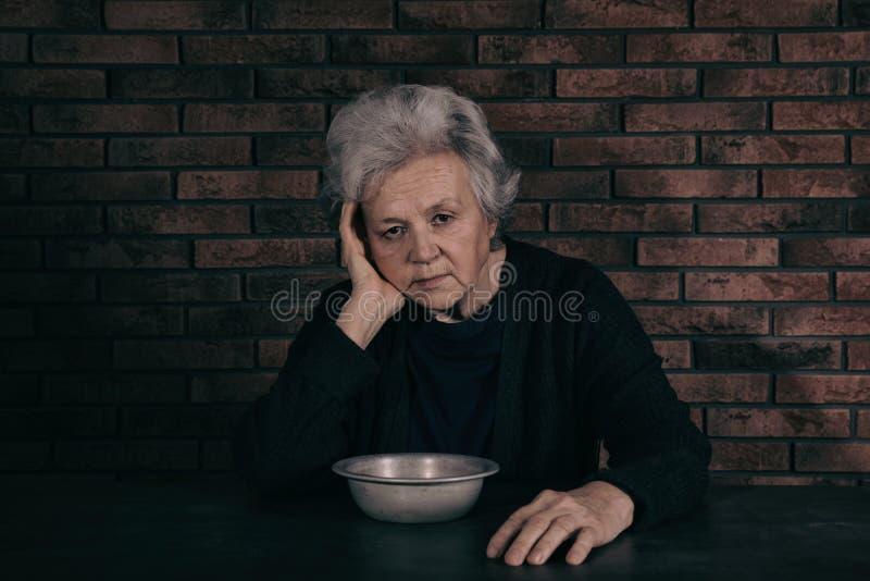 Donna matura povera con la ciotola fotografie stock libere da diritti