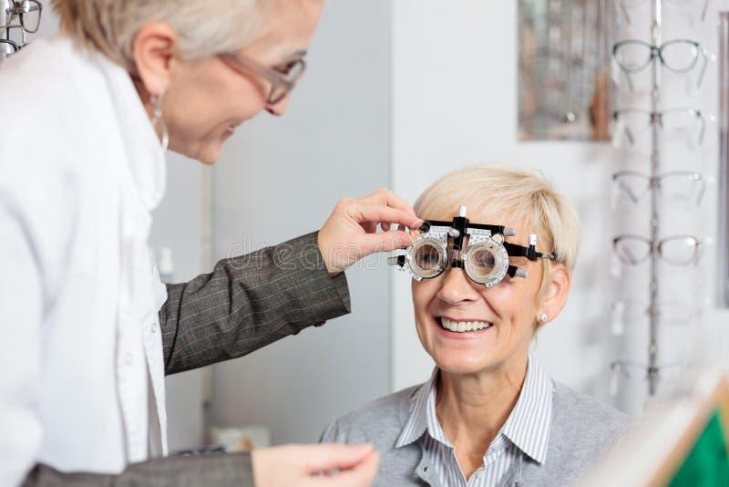 Donna matura sorridente che ha l'esame di vista e misura della diottria da un optometrista femminile alla clinica di oftalmologia fotografie stock libere da diritti