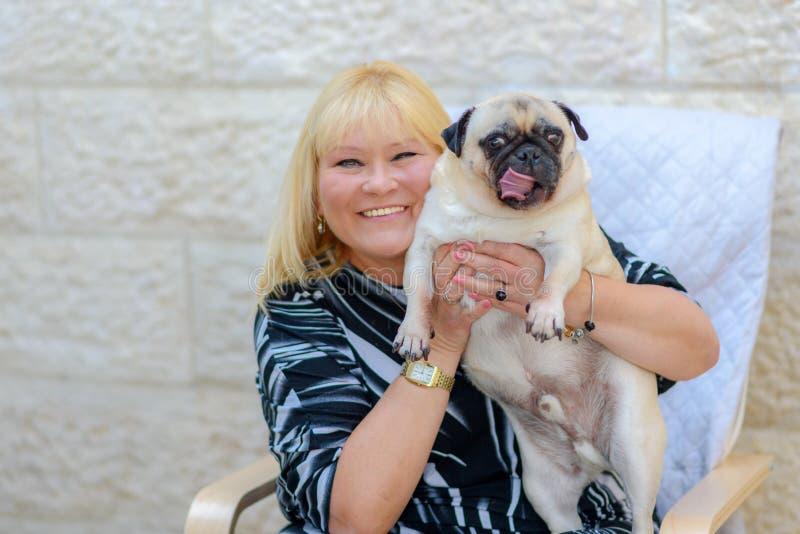 Donna matura sorridente felice con il cane di animale domestico all'aperto immagine stock