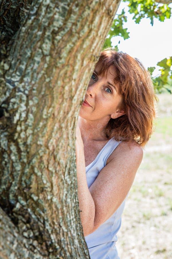 Donna matura splendida che si nasconde dietro un albero per la metafora di discrezione fotografia stock libera da diritti