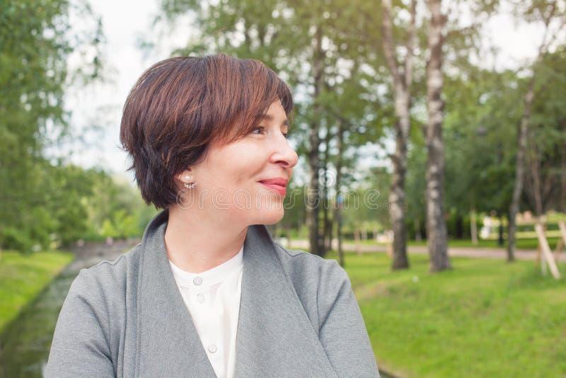 Donna matura sveglia che si rilassa all'aperto Fine femminile del fronte sul ritratto, profilo immagini stock libere da diritti