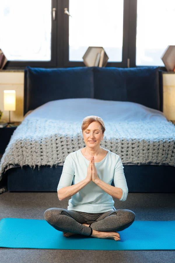 Donna matura tranquilla in vestiti comodi che fanno yoga in suo appartamento alla moda fotografia stock libera da diritti