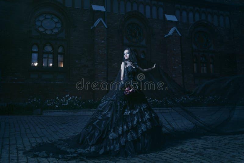 Donna misteriosa in vestito nero vicino a chirch fotografia stock libera da diritti