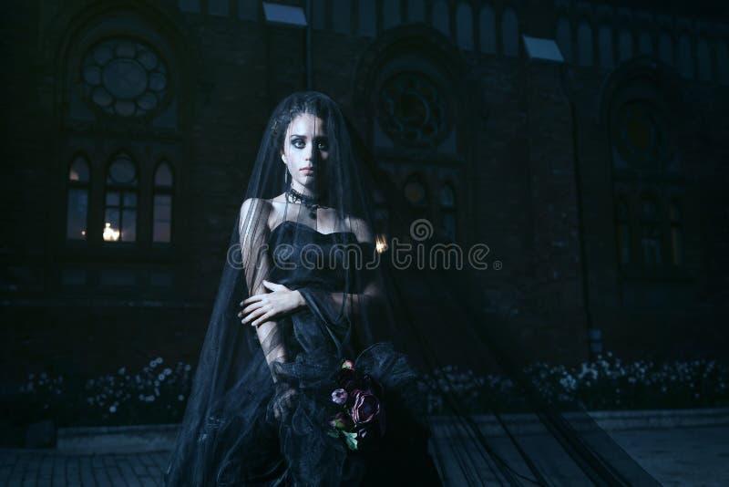 Donna misteriosa in vestito nero vicino a chirch immagine stock libera da diritti