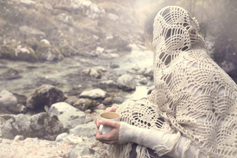 Donna mistica che beve un tè caldo che affronta il fiume immagini stock