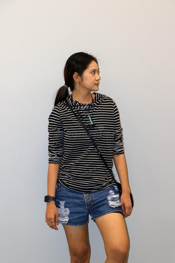 Donna moderna asiatica nel colore bianco e nero delle bande della maglietta a maniche lunghe, stante ed affrontante al lato fotografia stock libera da diritti