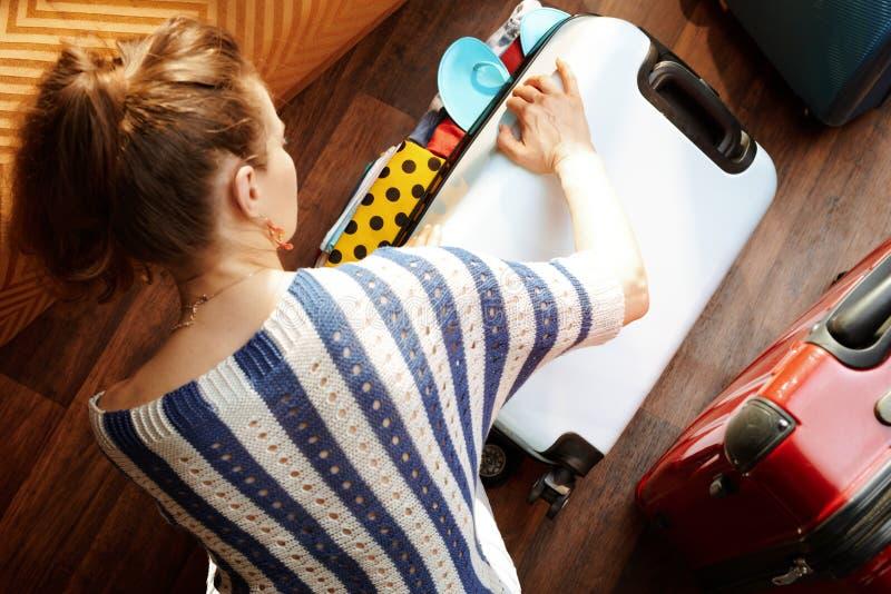 Donna moderna che si chiude sopra la valigia imballata immagini stock