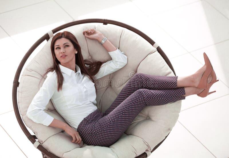 Donna moderna che si rilassa in una sedia rotonda comoda fotografia stock libera da diritti