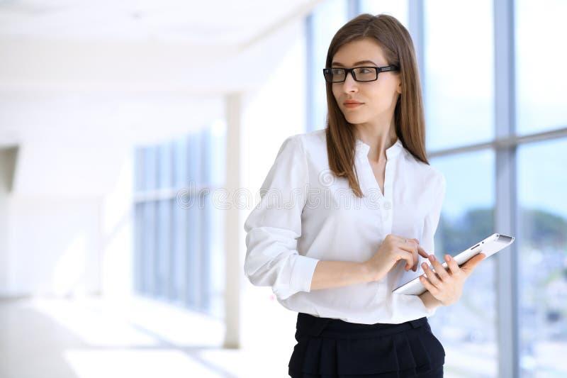 Donna moderna di affari che scrive sul computer portatile mentre stando nell'ufficio prima incontrarsi o della presentazione immagine stock
