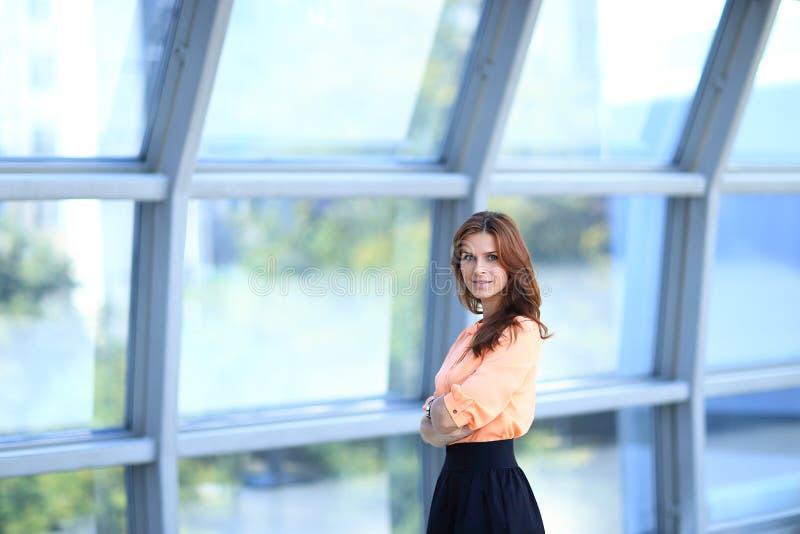 Donna moderna di affari che sta vicino ad una grande finestra nell'ufficio immagini stock libere da diritti