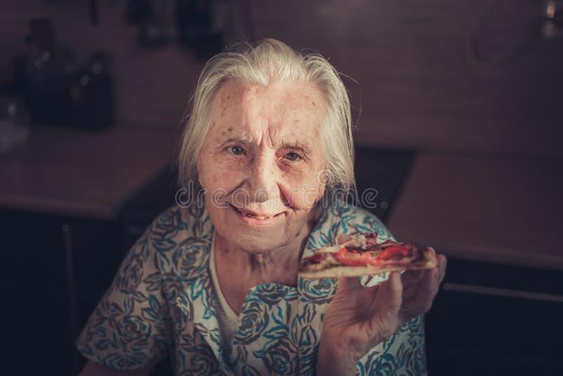 Donna molto anziana che mangia un pezzo di pizza a casa fotografia stock libera da diritti