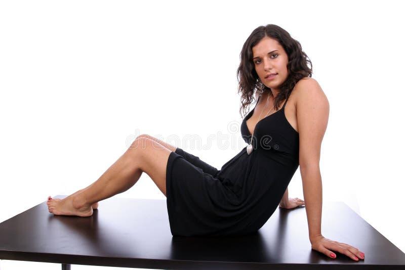 Donna molto attraente, proponente su uno scrittorio fotografie stock libere da diritti