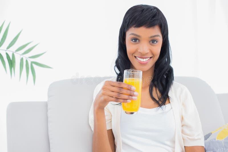 Donna mora adorabile in vestiti bianchi che beve succo d'arancia immagine stock libera da diritti